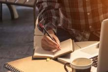 A person writing in a day planner while sitting in front of a laptop computer.